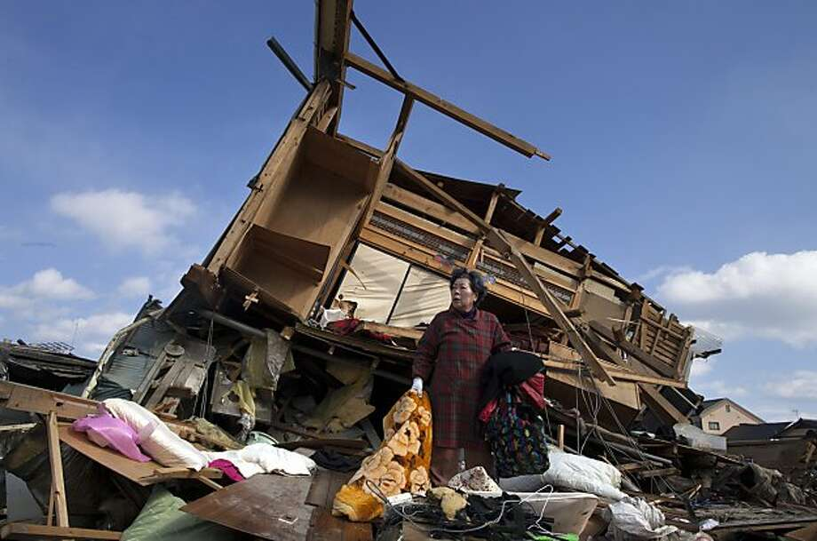 Aiko Musashi is stunned as she looks at her neighbour's house while collecting personal belongings at her destroyed home on March 18, 2011 in Kesennuma, Japan. Thousands have been killed as a result of the 9.0 earthquake andconsequent tsunami that struck the northeast coast of Japan six days ago. A potential humanitarian crisis looms as nearly half a million people who have been displaced by the disaster continue to suffer a shortage of food and fuel as freezing weather conditions set in. Photo: Paula Bronstein, Getty Images