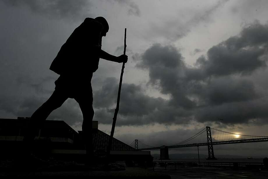 The Ghandi statue on Ferry Plaza along the Embarcadero is silhouetted against the cloudy skies that fill San Francisco Bay on Friday March 18, 2011. Photo: Michael Macor, The Chronicle