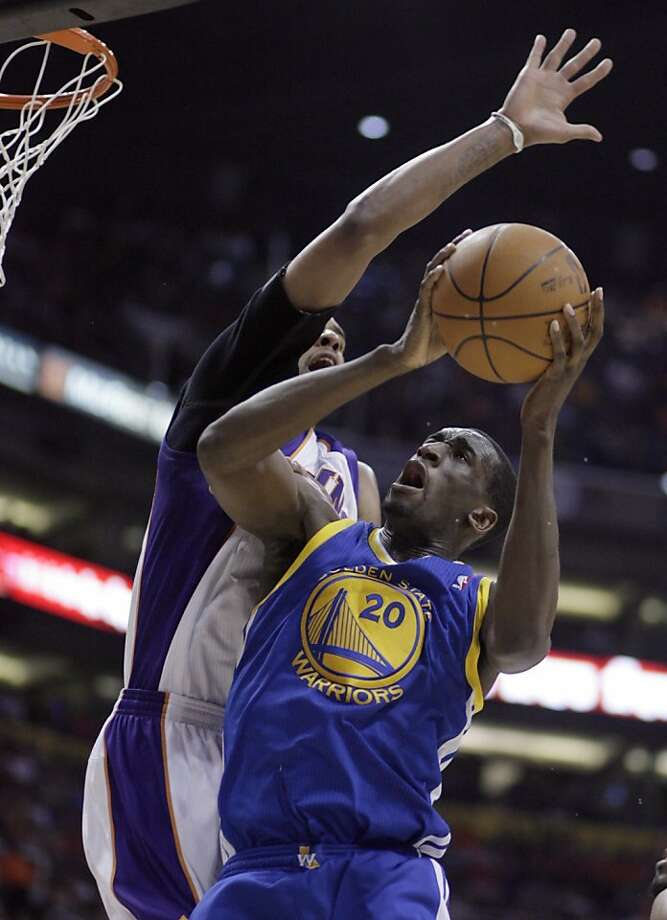 Golden State Warriors forward Ekpe Udoh, right, drives to the basket past Phoenix Suns forward Channing Frye, left, in the third quarter of an NBA basketball game Friday, March 18, 2011, in Phoenix. The Suns won 108-97. Photo: Paul Connors, AP