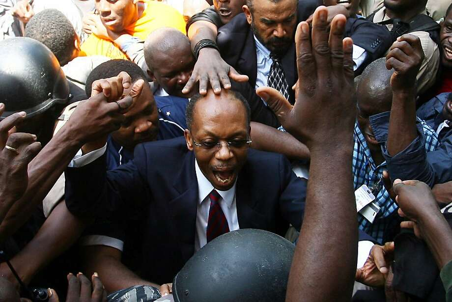 Former Haitian President Jean Bertrand Aristide (C) is greeted by supporters in Port-au-Prince on March 18, 2011. The return of Aristide, after seven years of exile in South Africa, comes ahead of a presidential run-off vote on Mach 20 that could offer some stability to a country reeling from a devastating 2010 earthquake and political turmoil.   TOPSHOTS/ Photo: Hector Retamal, AFP/Getty Images