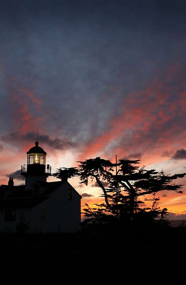The sun sets behind the historic Point Pinos lighthouse in Pacific Grove, Calif., on Sunday, Feb. 20, 2011. The beacon has been guiding mariners sailing near the Monterey Peninsula's rugged coastline since 1855 and is the oldest continuously operating beacon on the west coast. For a suggested donation of $2, visitors can tour lighthouse Thursday through Monday from 1 p.m. to 4 p.m. Photo: Paul Chinn, The Chronicle