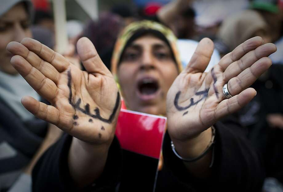 """A Libyan woman reacts with her hands written on them in Arabic """" I love Libya' as she joins a rally in support of the allied air campaigns against the forces of Moammar Gadhafi in Benghazi, eastern Libya, Wednesday, March 23, 2011. Photo: Anja Niedringhaus, AP"""