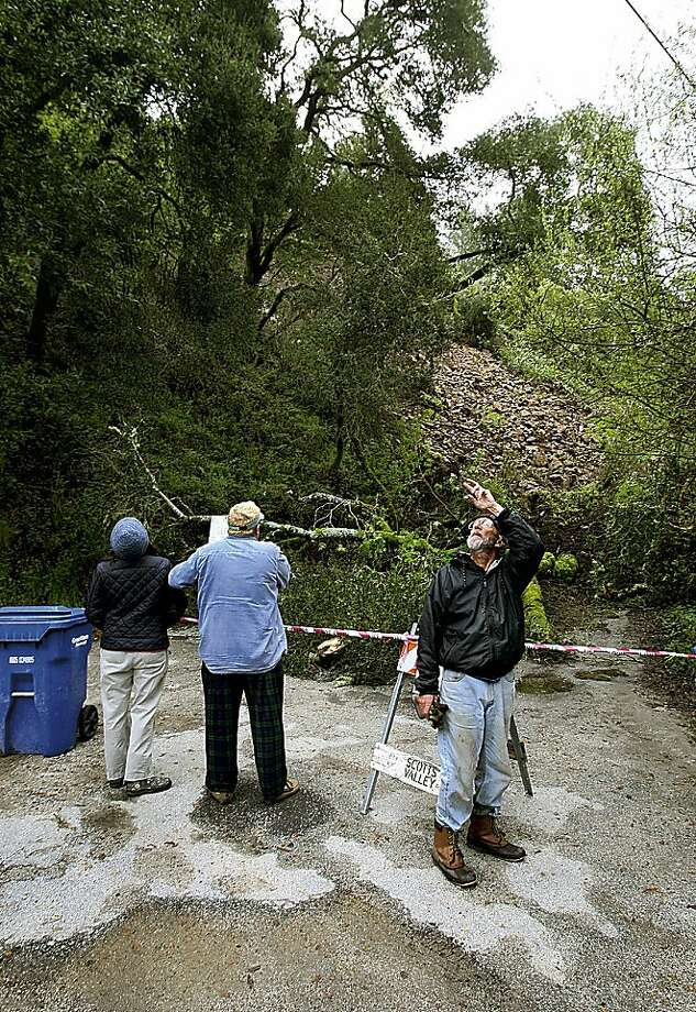 Bob Orser, right, looks at power lines after a rock slide cut off 26 homes in Scotts Valley on Tuesday. Clearing the slide could take anywhere from a day to two weeks, officials said, and rain forecast for this weekend could cause the slide to shift more. Photo: Dan Coyro, AP