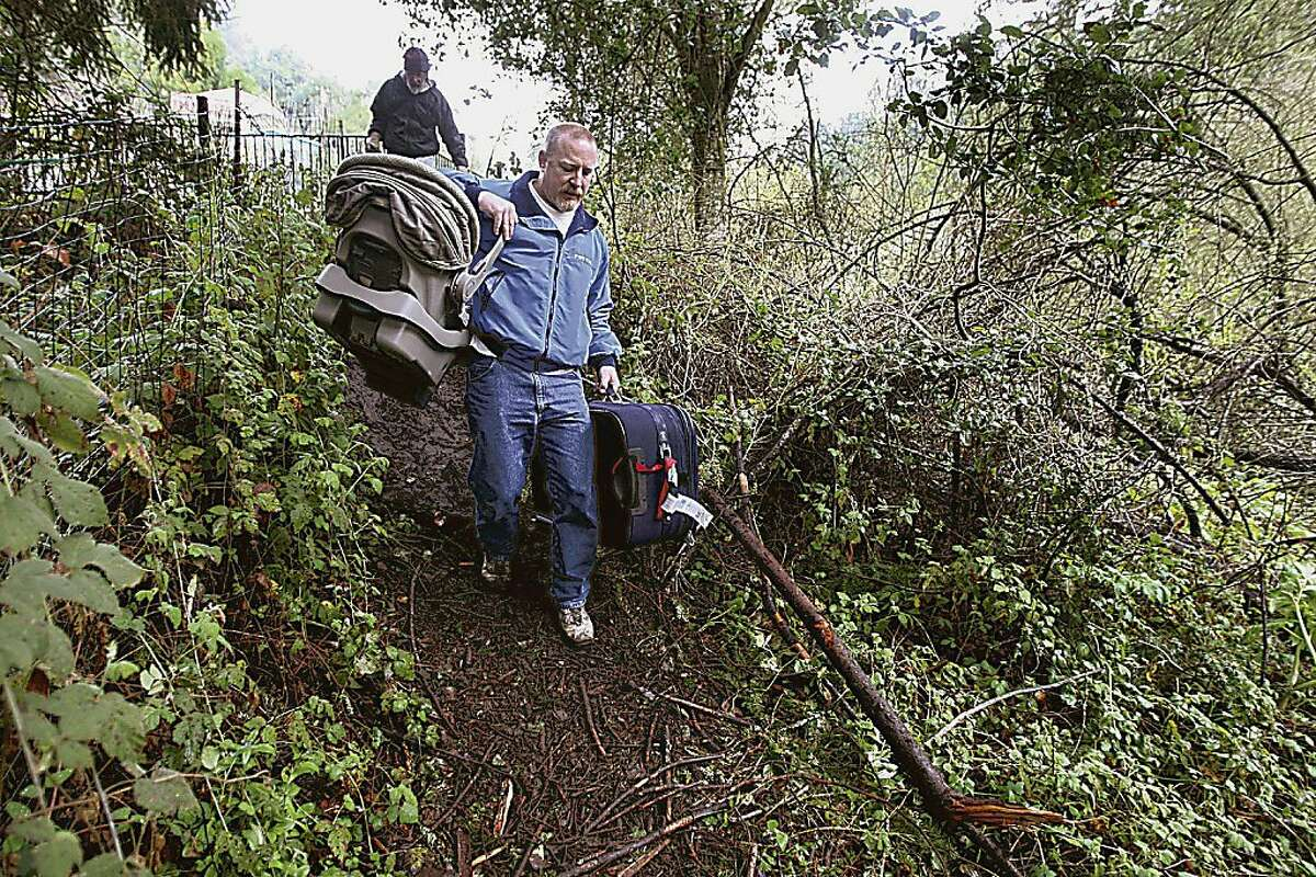 Mark Duncan hauls his things to his truck after a rock slide blocked his way in Scotts Valley on Tuesday. Clearing the slide could take anywhere from a day to two weeks, officials said, and rain forecast for this weekend could cause the slide to shift more.