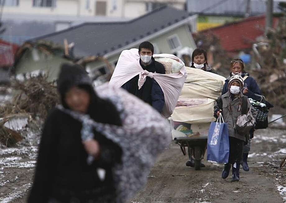 Survivors of Friday's earthquake and tsunami carry their belongings picked up from their damaged houses in Higashimatsushima, Miyagi Prefecture, northern Japan, Thursday, March 17, 2011. Photo: Kazuki Wakasugi, AP