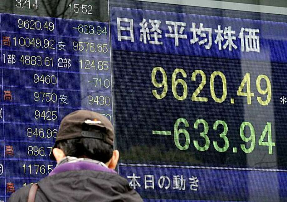 A man looks at a stock price board in Tokyo Monday, March 14, 2011 as the Tokyo stock market plunged on its first business day after an earthquake and tsunami of epic proportions laid waste to cities along Japan's northeast coast. The benchmark Nikkei 225stock average slid 633.94 points, or 6.2 percent, to 9,620.49, extending losses from Friday. Photo: Eugene Hoshiko, AP
