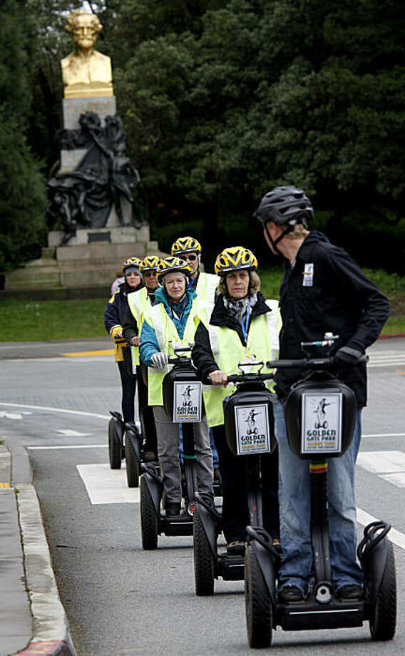 The Segway tour drives in the bike lane past the California Academy of Sciences Sunday March 13, 2011. Segway tours in Golden Gate Park in San Francisco, Calif. are a new popular way to see the sights, but a small group of people don't like the latest commercialization of their park. Photo: Brant Ward, The Chronicle