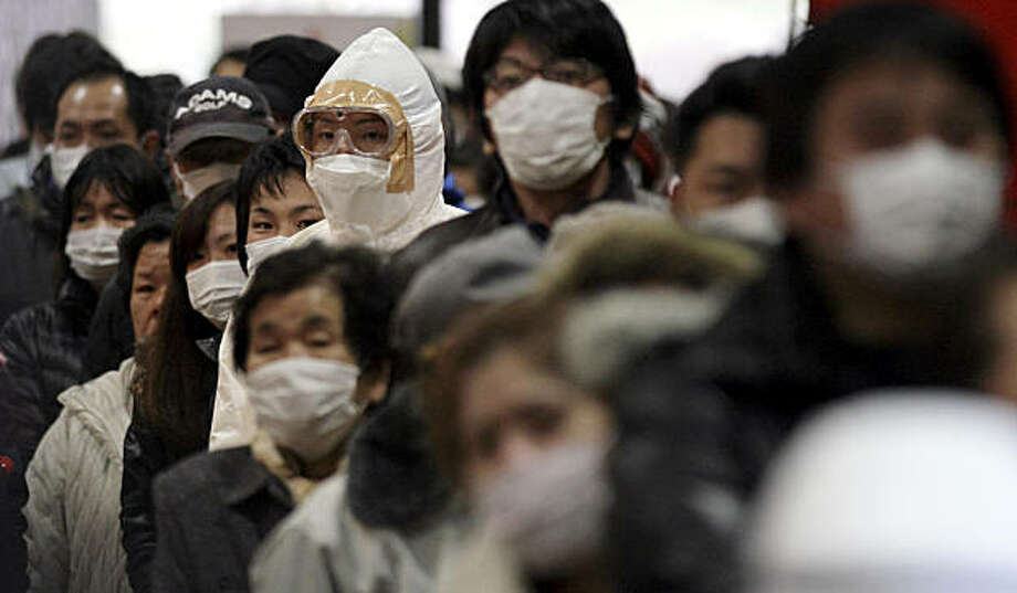 An official in protective clothing stands with residents at they wait in a line to be scanned for radiation at a temporary scanning center for residents living close to the quake-damaged Fukushima Dai-ichi nuclear power plant Wednesday, March 16, 2011, inKoriyama, Fukushima Prefecture, Japan. Photo: Gregory Bull, AP