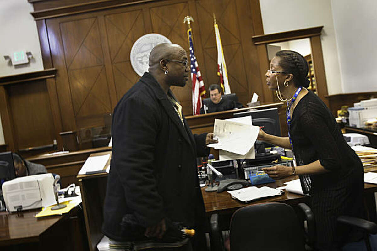 Jimmie Fails of San Francisco collects paper work from Gwendolyn Bates, deputy probation officer, after hearing that his probation is shortened by 2 months after a non-required appearance at the Community Justice Center on Tuesday, March 15, 2011 in SanJimmie Fails of San Francisco collects paper work from Gwendolyn Bates, deputy probation officer, after hearing that his probation is shortened by 2 months after a non-required appearance at the Community Justice Center Court on Tuesday, March 15, 2011 in San Francisco, Calif.