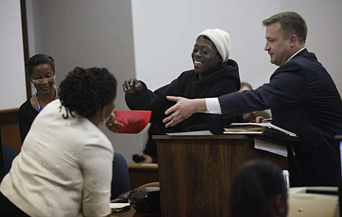 Tomiquia Moss (l to r), Community Justice Center coordinator, hands a bowl of candy to Lacrecia Hicks of San Francisco while attorney Russell Goodrow assits while appearing at the Community Justice Center Court on Tuesday, March 15, 2011 in San Francisco, Calif.
