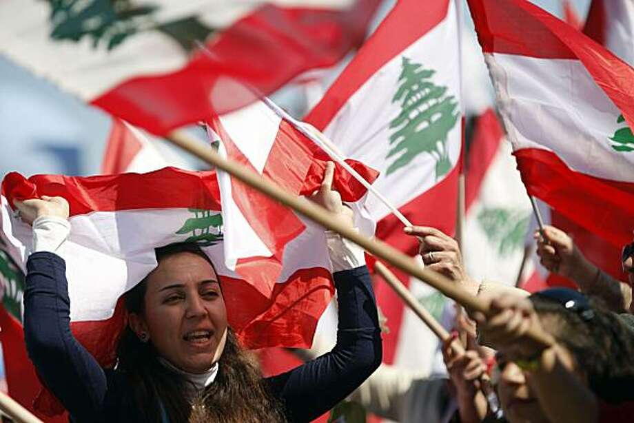 BEIRUT, LEBANON - MARCH 13: A protester waves a Lebanese flag during a demonstration on March 13, 2011 in Beirut, Lebanon.  Tens of thousands of Lebanese opposition supporters demanded Hezbollah be disarmed as they rallied to mark the sixth anniversary ofa popular uprising against Syrian troops in the country. Photo: Salah Malkawi, Getty Images
