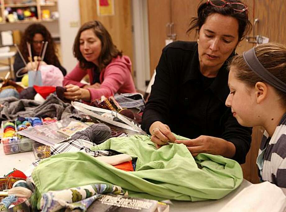 Sherri Lynn Wood (right) helps Sonia Hauser, 12, (far right) with mending a pair of Hauser's pants during a kitting and mending class that is part of a How-to Homestead event series at the Harvey Milk Recreational Arts Center in San Francisco, Calif., on Saturday, March 5, 2011. Photo: Thomas Levinson, The Chronicle
