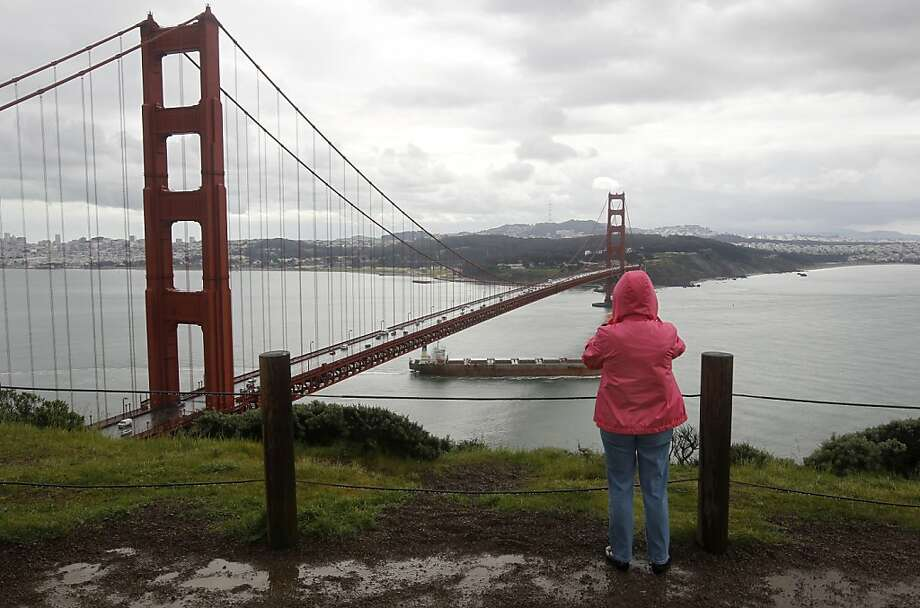 A visitor watches a ship pass under the Golden Gate Bridge from Battery Spencer in the Marin Headlands on Thursday, Feb. 24, 2011. Photo: Paul Chinn, The Chronicle