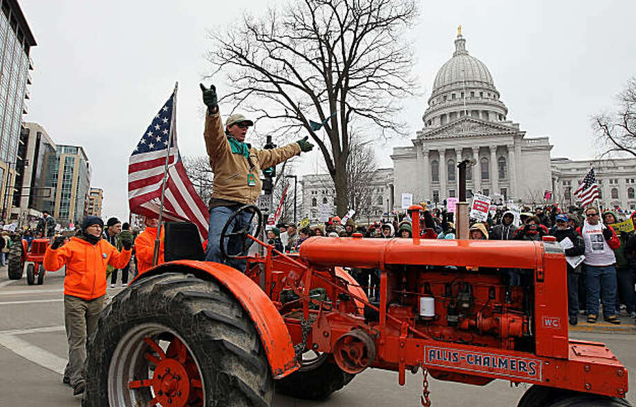"MADISON, WI - MARCH 12:  A farmer waves his arms as he drives his tractor in a ""tractorcade"" during a demonstration outside of the Wisconsin State Capitol on March 12, 2011 in Madison, Wisconsin. Tens of thousands of protestors staged a massive demonstration outside of the Wisconsin State Capitol one day after Gov. Scott Walker signed his controversial budget repair bill into law. Photo: Justin Sullivan, Getty Images"