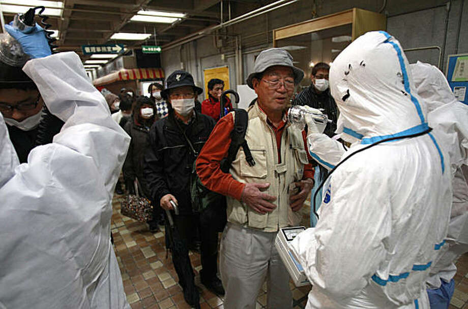 An evacuee is screened for radiation exposure at a testing center Tuesday, March 15, 2011, in Koriyama city, Fukushima prefecture, Japan, after a nuclear power plant on the coast of the prefecture was damaged by Friday's earthquake. Photo: Wally Santana, AP