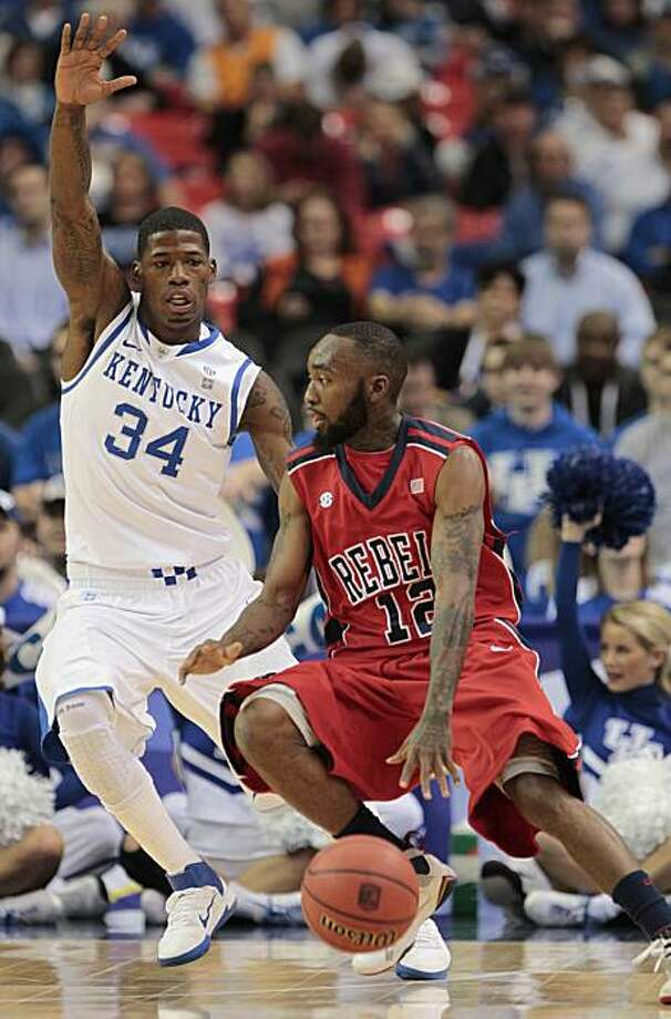 Mississippi guard Chris Warren (12) moves the ball as Kentucky guard DeAndre Liggins (34) defends during the first half  of an NCAA college basketball game at the Southeastern Conference tournament, Friday, March 11, 2011, in Atlanta. Photo: Dave Martin, AP