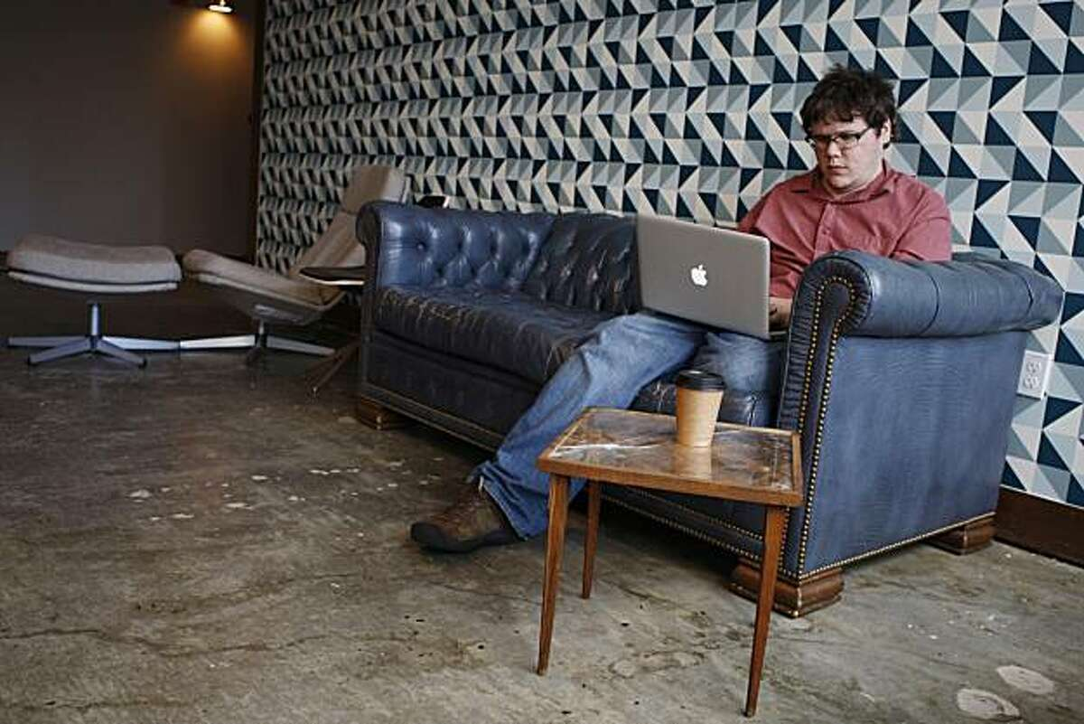 Matthew O'Connor works while sitting on a vintage couch at the Square office in San Francisco Calif, on Thursday, March 3, 2011.