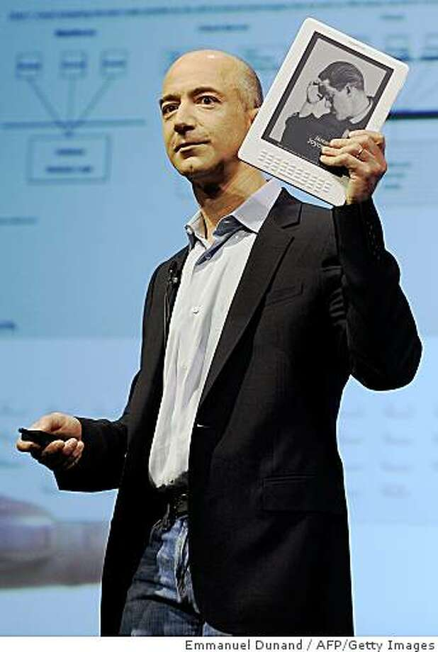 Online retail giant Amazon.com CEO Jeff Bezos unveils the Kindle DX, a large-screen version of its popular Kindle electronic reader designed for newspapers, magazines and textbooks, during a press conference in New York, May 06, 2009.  The Kindle DX costs 489 dollars and features a screen which at 9.7 inches (24.6 centimeters) is 2.5 times larger than the six-inch (15.24 cm) screen on the earlier versions of the Kindle, which cost 359 dollars. TOPSHOTS/AFP PHOTO/Emmanuel Dunand (Photo credit should read EMMANUEL DUNAND/AFP/Getty Images) Photo: Emmanuel Dunand, AFP/Getty Images