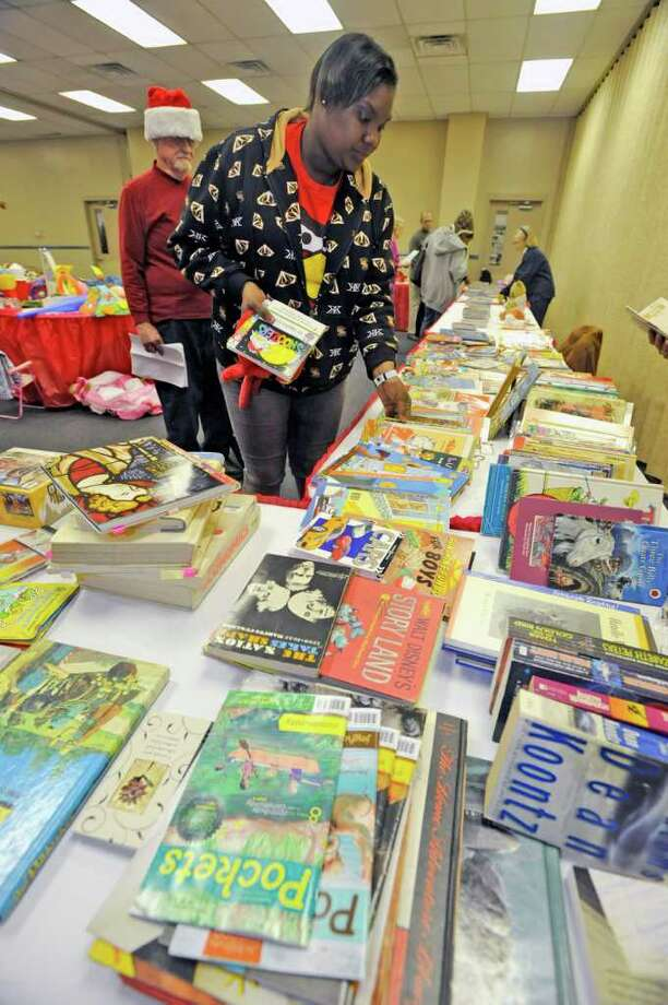 Genera Granger, right, looks over books for her twins with the help of Volunteer Albert Broussard, left, who was carrying her bag. The second day of toy and book distribution from the Empty Stocking Fund at the Beaumont Civic Center Wednesday. Families will be picking up their toys through Thursday as well, which is the last day of the annual event. Dave Ryan/The Enterprise