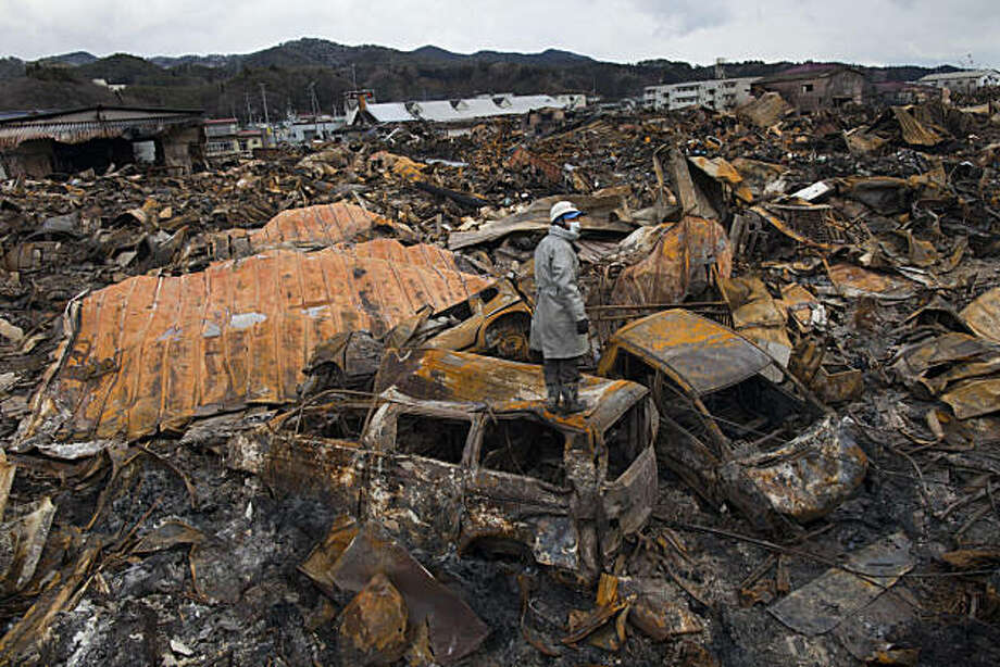 KESENNUMA, JAPAN - MARCH 16:  A rescue worker stands on top of a burned vehicle looking for more bodies hidden amongst the rubble of a village destroyed by the devastating earthquake, fires and tsunami March 16, 2011 in Kesennuma, Miyagi province, Japan.The 9.0 magnitude strong earthquake struck offshore on March 11 at 2:46pm local time, triggering a tsunami wave of up to ten metres which engulfed large parts of north-eastern Japan. As the death toll continues to rise, the country is also struggling to contain a potential nuclear meltdown after the nuclear plant was seriously damaged from the quake. Photo: Paula Bronstein, Getty Images