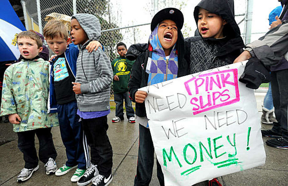 Students join several hundred teachers and parents protesting teacher layoffs on Tuesday, March 15, 2011, in Oakland, Calif. At right are first grader Malik Pedraza-Palominos, right, and kindergarten student Devin Haynes, second fron right,  from Henry J. Kaiser, Jr. Elementary School. Photo: Noah Berger, Special To The Chronicle