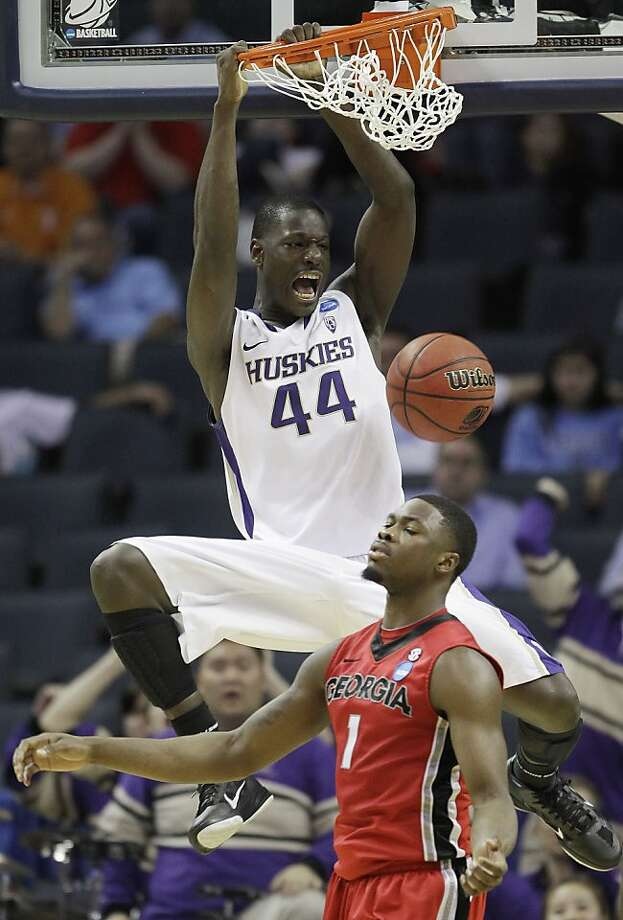 Washington forward Darnell Gant (44) dunks the ball as Georgia guard Travis Leslie (1) reacts in the second half of a East Regional NCAA tournament second round college basketball game, Saturday, March 19, 2011, in Charlotte, N.C. Photo: AP