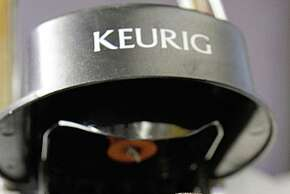 FILE-In this Oct. 7, 2010, file photo, a Green Mountain Coffee single-serving brewing cup is seen in a Keurig machine in Montpelier, Vt.  Starbucks Corp. and Green Mountain Coffee Roasters Inc. say they have reached a deal that will bring single-cup Starbucks coffee and Tazo tea pods to Keurig users. Starbucks has been looking to beef up its presence in the fast-growing single-cup coffee market and Green Mountain is considered one of its leaders.