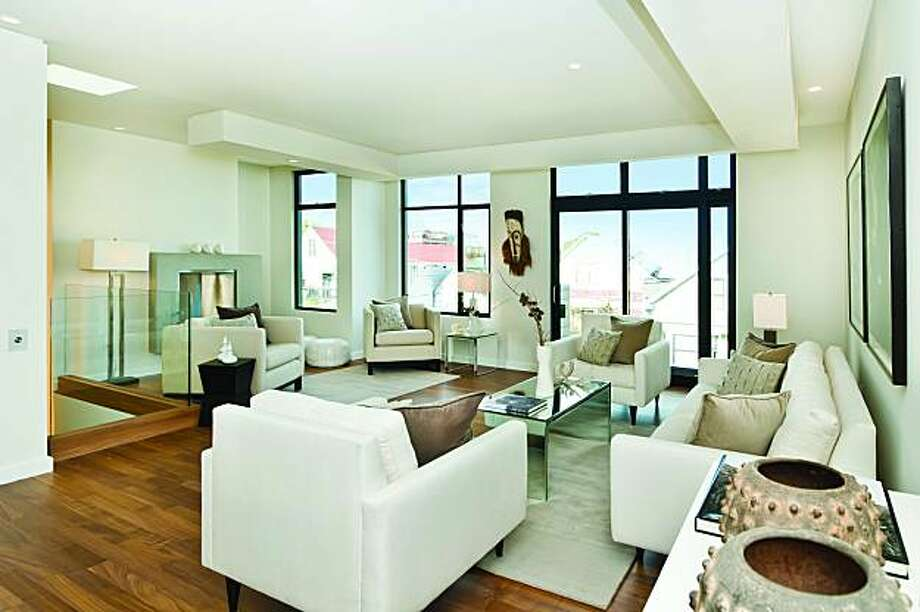 An upper living room room has recessed lighting, a fireplace, picture windows and glass doors that open to a front balcony. Photo: Olga Soboleva, Vanguard Properties