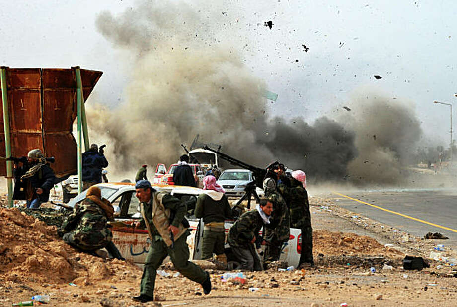 Shrapnels fly through the air as a tank shell explodes near Libyan rebel fighters defending their last position against Moamer Kadhafi's loyalist forces at the north-central key Libyan oil town of Ras Lanuf on March 10, 2011. Photo: Roberto Schmidt, AFP/Getty Images