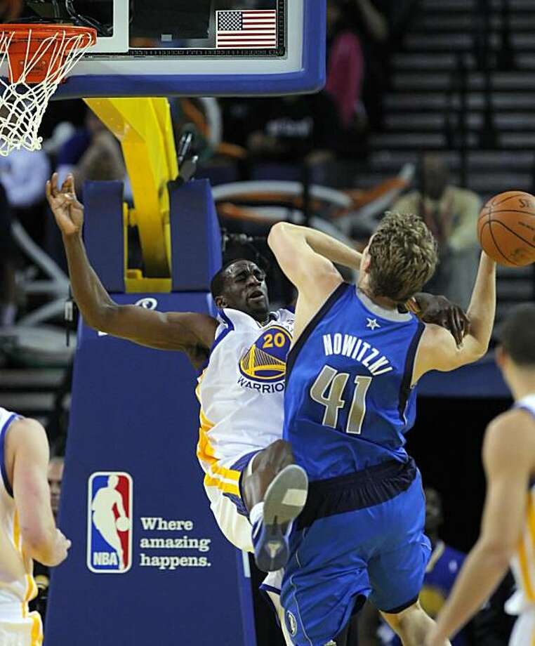 Ekpe Udoh is knocked back as he fouls Dirk Nowitzki in the second half. Nowitzki had 34 points for the Mavericks. The Golden State Warriors played the Dallas Mavericks at Oracle Arena in Oakland, Calif., on Wednesday, March 16, 2011. Photo: Carlos Avila Gonzalez, The Chronicle