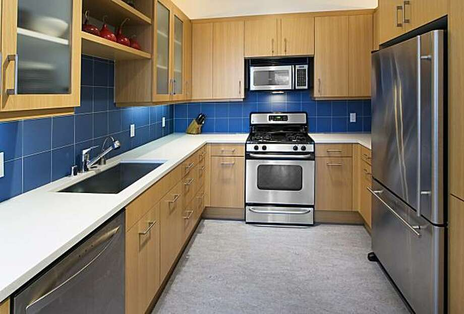 A blue ceramic backsplash highlights the updated kitchen, which offers stainless steel appliances, plenty of cabinet space and Caesarstone counters. Photo: Steph Dewey, Reflex Imaging