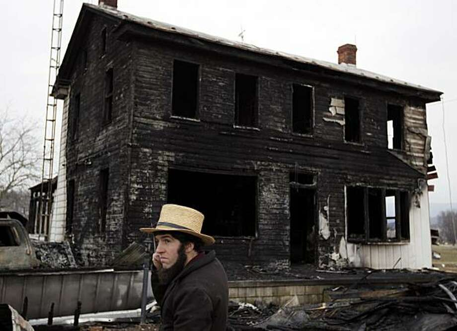 A neighbor stands near the fire ravaged farmhouse of Theodore and Janelle Clouse Wednesday, March 9, 2011, in Loysville Pa. Seven Clouse children including a 7-month-old infant, perished in a fast-moving fire at the home early Wednesday morning, March 9,2011, while their mother milked cows and their father dozed in a milk truck down the road. Photo: Carolyn Kaster, AP