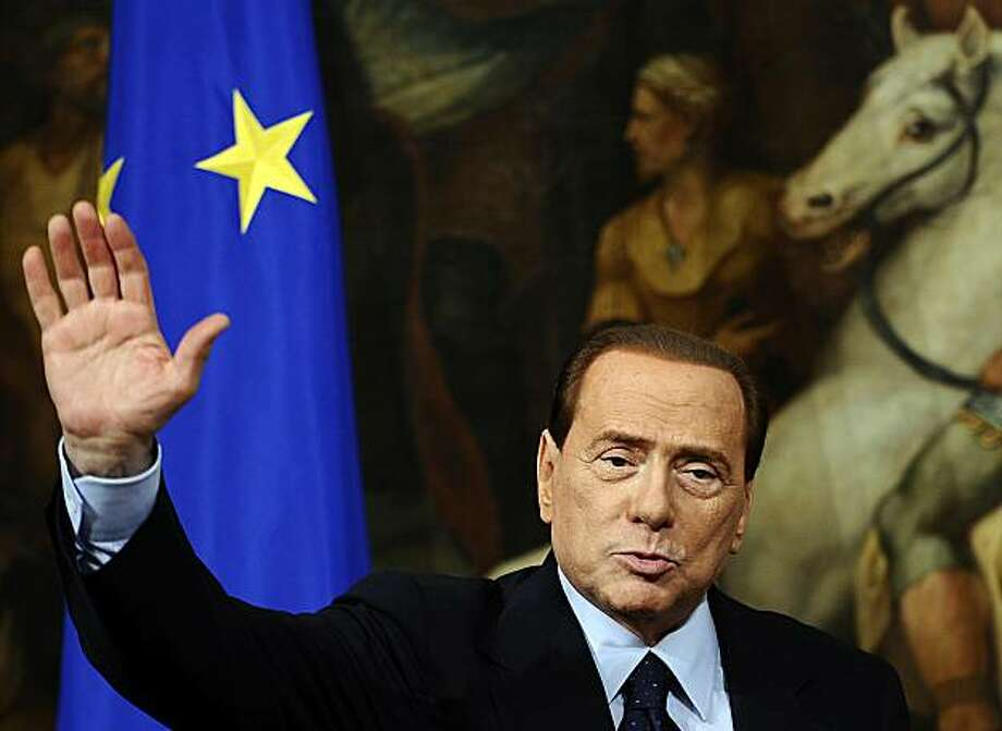 Italian Prime Minister Silvio Berlusconi waves during a joint press conference with European Union commission President Jose Manuel Barroso (not pictured) following their meeting on March 14, 2011 at Palazzo chigi in Rome. Photo: Filippo Monteforte, AFP/Getty Images