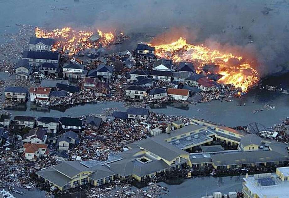 Houses are in flame while the Natori river is flooded over the surrounding area by tsunami tidal waves in Natori city, Miyagi Prefecture, northern Japan, March 11, 2011, after strong earthquakes hit the area. (AP Photo/Yasushi Kanno, The Yomiuri Shimbun)  JAPAN OUT, CREDIT MANDATORY Photo: Yasushi Kanno, Associated Press