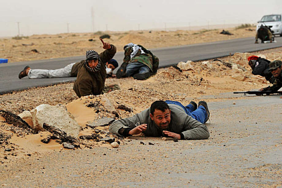 Libyan rebel fighters try to cover as shells explode nearby, a few kilometers from Bin Jawad on March 8, 2011. Photo: Roberto Schmidt, AFP/Getty Images
