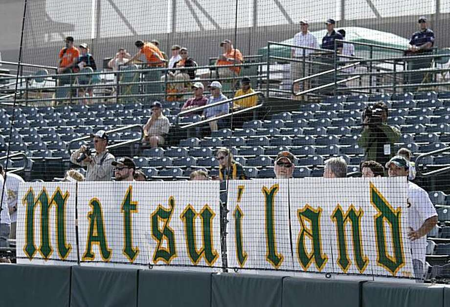 A group of fans at Phoenix Municipal Stadium hold up a large sign as the Oakland Athletics' Hideki Matsui takes batting practice before their spring training baseball game against the San Francisco Giants in Phoenix, Saturday, March 5, 2011. Photo: Eric Risberg, AP