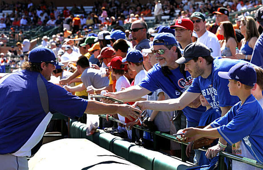 The Dodgers' Russell Mitchell signs autographs for Jeremy Teaguarden, second from left, prior to the start of their spring training game at Scottsdale Stadium in Scottsdale, Ariz., on Saturday. Photo: Lance Iversen, The Chronicle