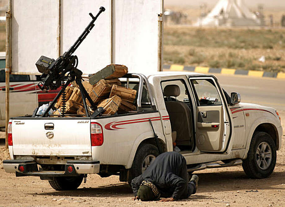 A Libyan rebel prays next to a pick-up truck loaded with a machinegun in Ajdabiya, a key town which the rebels have vowed to defend at all costs from forces loyal to Libyan leader Moamer Kadhafi, on March 14, 2011. Photo: Patrick Baz, AFP/Getty Images