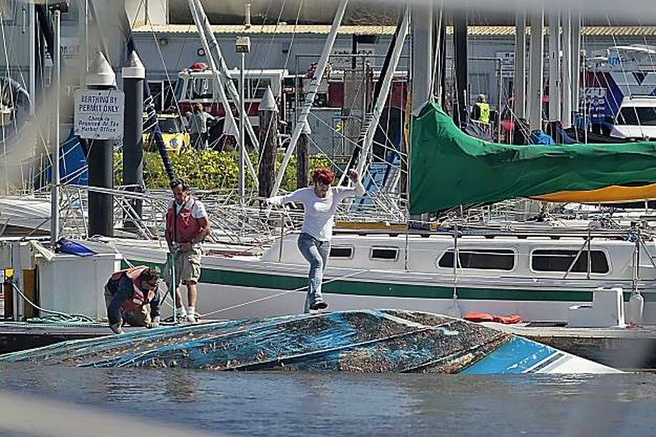 A boat owner jumps onto her sinking boat  as people from the Vessel Assist try to secure it as the tsunami waters  surge in and out of  Santa Cruz Harbor, Friday March 11, 2011,  in Santa Cruz, Calif. Photo: Lacy Atkins, The Chronicle