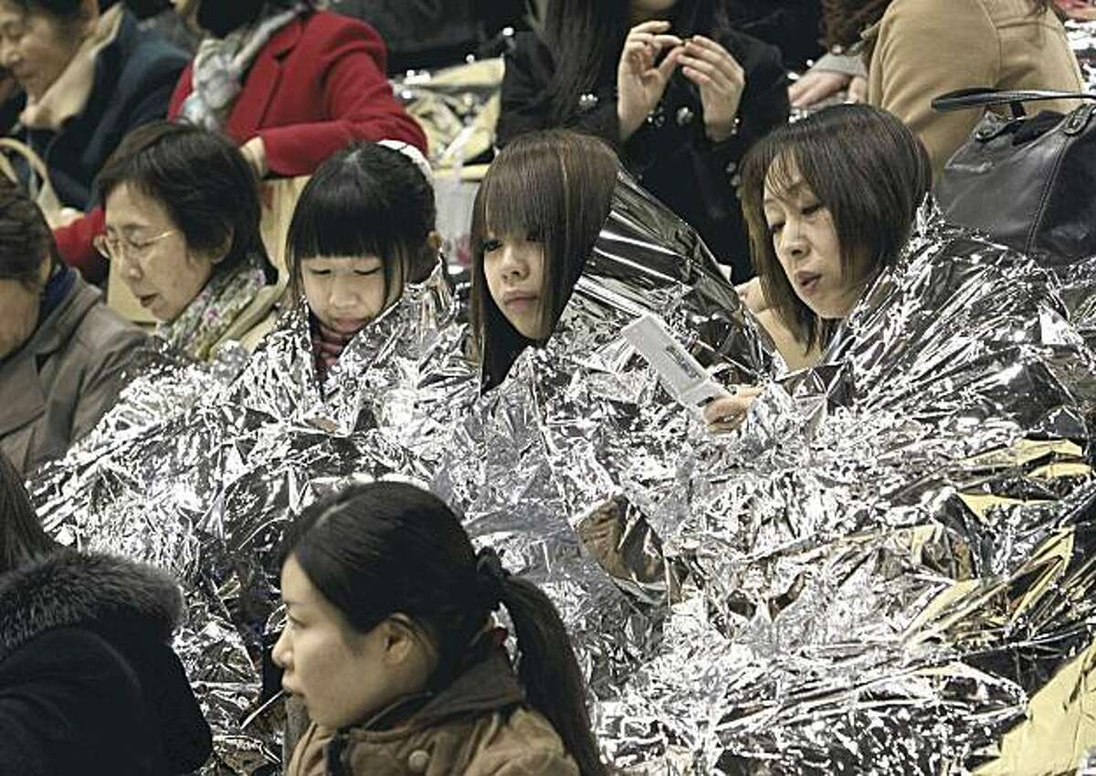 Women wrapped themselves up in disaster sheets sit together at a temporary shelter set up at Aoyama Gakuin University in Tokyo for people who can't go home Friday, March 11, 2011. A powerful tsunami spawned by the largest earthquake in Japan's recorded history slammed the eastern coast Friday, sweeping away boats, cars, homes and people as widespread fires burned out of control. (AP Photo/The Yomiuri Shimbun, Reiri Kurihara) JAPAN OUT, CREDIT MANDATORY