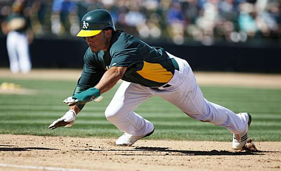 Oakland Athletics Coco Crisp dives safely back into first base during their spring training game with the Los Angeles Dodgers at Phoenix Municipal Stadium, Ariz. Friday, March 11, 2011. Photo: Lance Iversen, The Chronicle