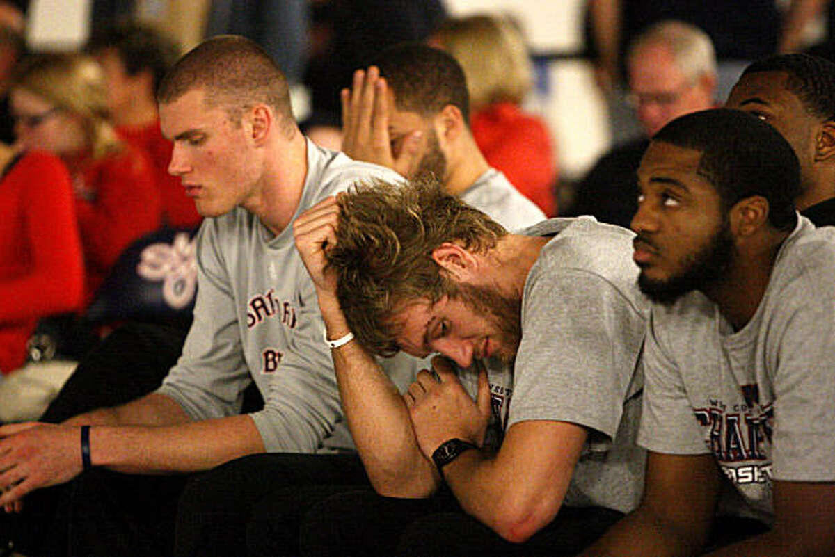 St. Mary's men's basketball players Phil Benson (left), Mitchell Young (center) and Kenton Walker II (right) react to finding out their team has not been invited to the NCAA Tournament in Moraga, Calif., on Sunday, March 13, 2011.