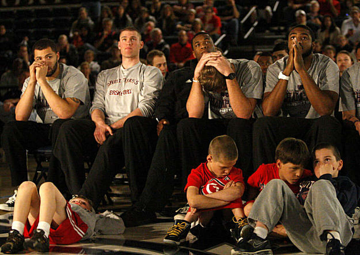 (From left to right) St. Mary's men's basketball team, Rob Jones, Phil Benson, Tim Williams, Mitchell Young, and Kenton Walker II, along with some young fans and relatives, react to finding out their team has not been invited to the NCAA Tournament, at McKeon Pavillion in Moraga, Calif., on Sunday, March 13, 2011.