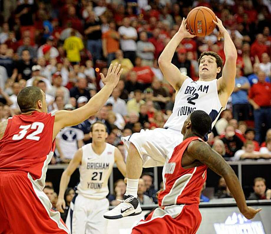 LAS VEGAS, NV - MARCH 11:  Jimmer Fredette #32 of the Brigham Young University Cougars shoots against Drew Gordon #32 and Jamal Fenton #13 of the New Mexico Lobos during a semifinal game of the Conoco Mountain West Conference Basketball tournament at theThomas & Mack Center March 11, 2011 in Las Vegas, Nevada. Fredette scored 52 points in BYU's 87-76 victory. Photo: Ethan Miller, Getty Images