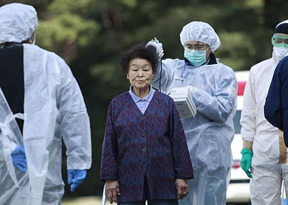Residents evacuated from areas surrounding the Fukushima nuclear facilities damaged in Friday's massive earthquake, are checked for radiation contamination, Sunday, March 13, 2011, in Koriyama city, Fukushima prefecture, Japan. Photo: Wally Santana, AP