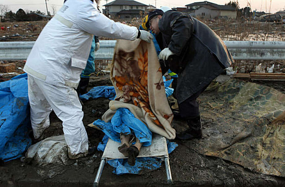 Workers move the body of a dead woman found in the Natori neighborhood of Sendai, Japan, on Sunday, March 13, 2011, that was hit hard by the tsunami in the aftermath of an 8.9 earthquake. Fires continue to burn in the neighborhood as civil servants are finally able to enter the area to search for victims. (Carolyn Cole/Los Angeles Times/MCT) Photo: Carolyn Cole, MCT