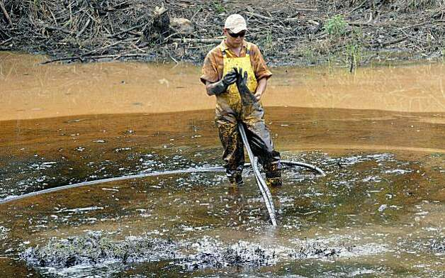 An employee of state-owned Petroecuador works on environmental cleansing operations of a 30-year old oil spillage at the Rumipamba commune, 200 mt from the Auca Sur 1 oil well --operated by US Chevron Texaco in the seventies--, in the province of Orellana, Amazonia, on February 20, 2011. Last week, a judge from the Sucumbios Provincial Court ordered US giant Chevron to pay USD 9,5 billion in compensation for environmental damages in the Ecuadorean Amazonia. Photo: Rodrigo Buendia, AFP/Getty Images