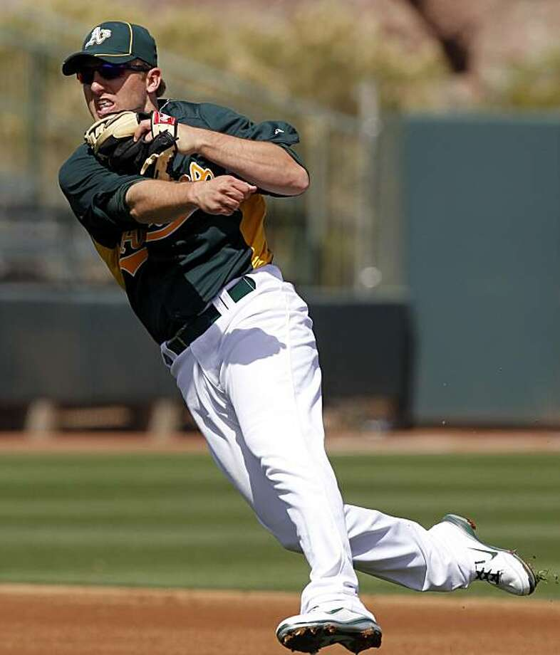 Oakland Athletics shortstop Cliff Pennington fails to throw out Kansas City Royals' Chris Getz at first during the first inning a spring training baseball game in Phoenix , Thursday, March 10, 2011. Photo: Chris Carlson, AP