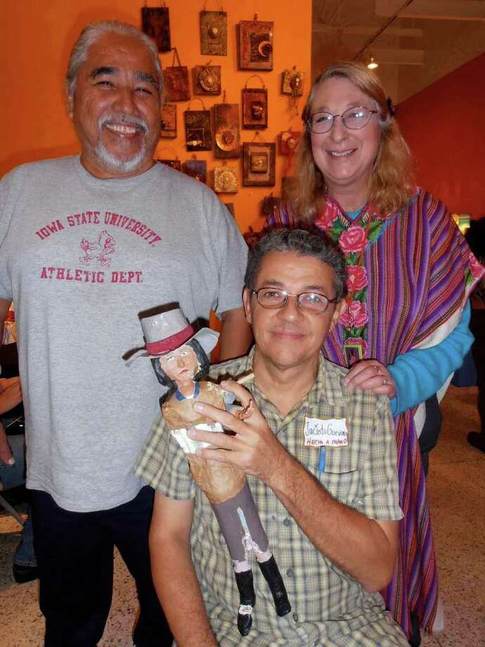 Photographer Jorge Sandoval, from left, meets up with Jacinto Guevara and Christine Saalbach at Hecho a Mano/Made by Hand, at the Guadalupe Cultural Arts Cen Photo: Nancy Cook-Monroe