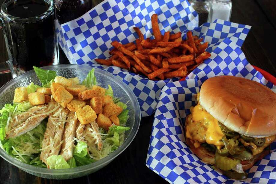 On the left is Armadillo's Caesar salad with grilled chicken, on the right is their jalapeno cheeseburger, and in the center (rear) is their sweet potatoe fries. (Thursday December 1, 2011) JOHN DAVENPORT/jdavenport@express-news.net Photo: SAN ANTONIO EXPRESS-NEWS